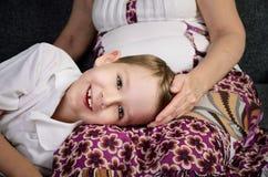 Lachender kleiner Junge, der Kamera betrachten und seine liebevolle Großmutter Stockbild