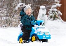 Lachender kleiner Junge fährt Spielzeugauto auf Schnee Stockbild