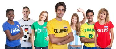 Lachender kolumbianischer Fan mit zujubelnder Gruppe anderer Fans Stockfoto