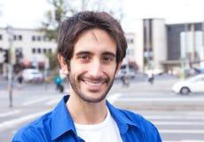 Lachender lateinischer Kerl in einem blauen Hemd in der Stadt Stockbild