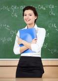 Lachender Lehrer an der Tafel übergibt ein Faltblatt stockbilder