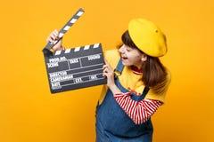 Lachender Mädchenjugendlicher im französischen Barett, Denim sundress, die auf klassischem schwarzem Filmherstellung clapperboard lizenzfreie stockfotos
