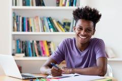 Lachender männlicher Student des Afroamerikaners, der für Diplom lernt lizenzfreie stockfotografie