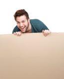 Lachender Mann, der leeres Plakat hält Stockfoto