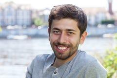 Lachender Mann mit Bart in einem grauen Hemd auf einem Fluss Stockbild