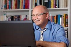 Lachender Mann mit Computer Stockbild