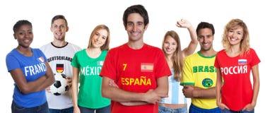 Lachender spanischer Fußballfan mit zujubelnder Gruppe anderer Fans Stockbild