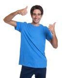 Lachender spanischer Kerl in einem blauen Hemd, das sich beide Daumen zeigt Lizenzfreies Stockfoto