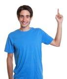 Lachender spanischer Kerl in einem blauen Hemd oben zeigend Stockfotos