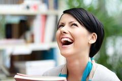 Lachender Student mit Buch an der Bibliothek stockfoto