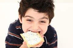 Lachender und essender Knall-scharfer Junge Stockfoto