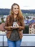 Lachender und trinkender Kaffee der schönen jungen Frau draußen stockbild