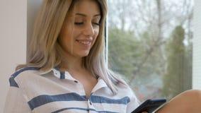 Lachender und trinkender Kaffee der sexy attraktiven Frau mit intelligentem Telefon in ihren Händen stock footage