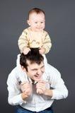 Lachender Vater, der ein seinen lächelnden kleinen Sohn anhält stockbild