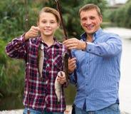 Lachender Vater mit dem Sohn, der Fische auf Haken betrachtet Lizenzfreie Stockfotografie