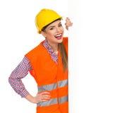 Lachender weiblicher Bauarbeiter And Banner Stockfoto