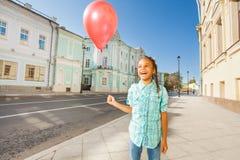 Lachendes afrikanisches Mädchen mit rotem Ballon in der Stadt Lizenzfreie Stockfotos