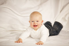 Lachendes Baby, das auf einer Couch liegt Stockfotografie