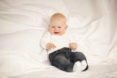 Lachendes Baby, das auf einer Couch sitzt Lizenzfreies Stockfoto