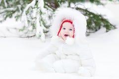 Lachendes Baby, das im Schnee unter einem Weihnachtsbaum sitzt Stockfotos
