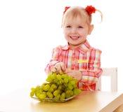 Lachendes blondes Essentraubensitzen des kleinen Mädchens Stockfotografie
