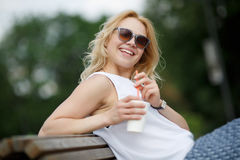 Lachendes blondes Mädchen in der Sonnenbrille, die auf Parkbank sitzt Lizenzfreies Stockfoto
