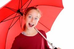 Lachendes blondes Mädchen mit rotem Regenschirm Lizenzfreie Stockfotos