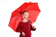 Lachendes blondes Mädchen mit rotem Regenschirm Lizenzfreies Stockfoto