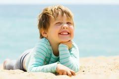 Lachendes dreijähriges Mädchen, das auf Strand legt Lizenzfreie Stockbilder