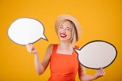 Lachendes entzückendes blondes Mädchen im Strohhut und im roten Abendkleid hält buble Fahnen der Sprache Gelber Hintergrund Stockfotografie