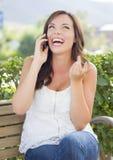 Lachendes jugendlich weibliches am Handy draußen sprechen auf Bank Lizenzfreie Stockfotografie