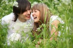 Lachendes junges Paar sitzt im Gras Stockbild