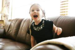 Lachendes Kind auf Sofa Stockbild
