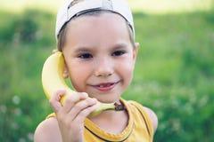 Lachendes Kind, beim Spielen mit einem hölzernen Bananentelefon vortäuschen Sie Lizenzfreies Stockbild
