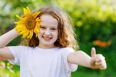 Lachendes Kind mit der Sonnenblume, Daumen zeigend lizenzfreies stockbild