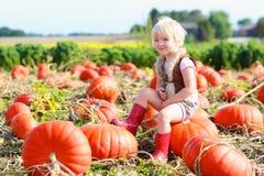 Lachendes kleines Mädchen, das auf Kürbisfeld spielt Lizenzfreies Stockfoto