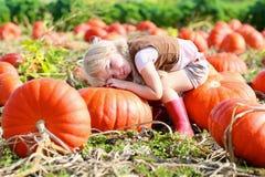 Lachendes kleines Mädchen, das auf Kürbisfeld spielt Lizenzfreie Stockfotografie
