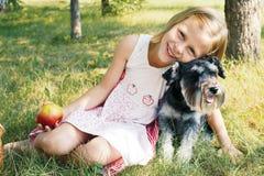 Lachendes kleines Mädchen, das ihren Hund umarmt Stockfotos