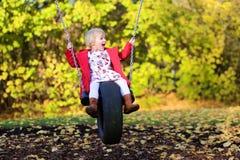 Lachendes kleines Mädchen, das im Park spielt Stockfotos