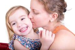 Lachendes kleines Mädchen, das von ihrer Mutter geküsst wird Lizenzfreie Stockbilder
