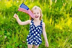 Lachendes kleines Mädchen mit dem langen blonden Haar, das amerikanische Flagge hält stockbilder