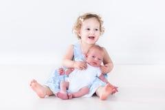 Lachendes Kleinkindmädchen mit ihrem neugeborenen Babybruder Lizenzfreie Stockfotografie