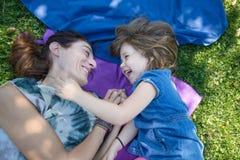 Lachendes Lügen des kleinen Mädchens und der Mutter im Park Lizenzfreie Stockfotografie