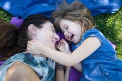 Lachendes Lügen des Mädchens und der Mutter im Park Stockbilder