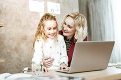 Lachendes langhaariges kleines Mädchen, das an Arbeit ihrer Mutter interessiert wird lizenzfreies stockbild
