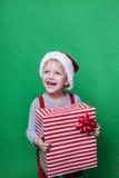 Lachendes lustiges Kind in rotem Hut Sankt, der in der Hand Weihnachtsgeschenk hält Weihnachtsniederlassung und -glocken Stockfotografie