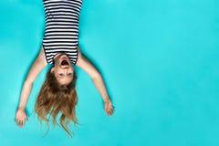 Lachendes Mädchen, das auf blauen Hintergrund herauf Seite festlegt lizenzfreie stockfotografie