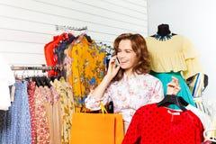 Lachendes Mädchen, das auf Mobile und dem Einkauf spricht Stockfoto