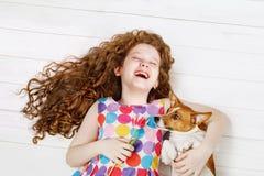 Lachendes Mädchen, das den Hund legt auf einen warmen Bretterboden umfasst lizenzfreies stockfoto