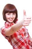 Lachendes Mädchen in einem Hemd, das Thumbs-up gibt Stockfotos